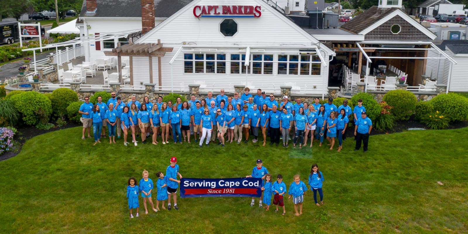 """The entire Captian Parkers staff gathered outside with a banner """"Serving Cape Cod Since 1981"""""""